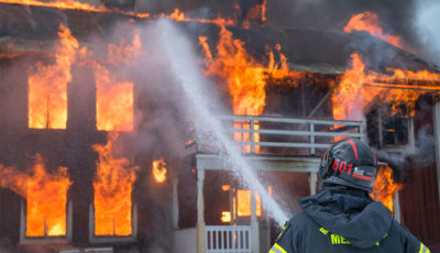 A firefighter sprays a jet of water onto a burning house
