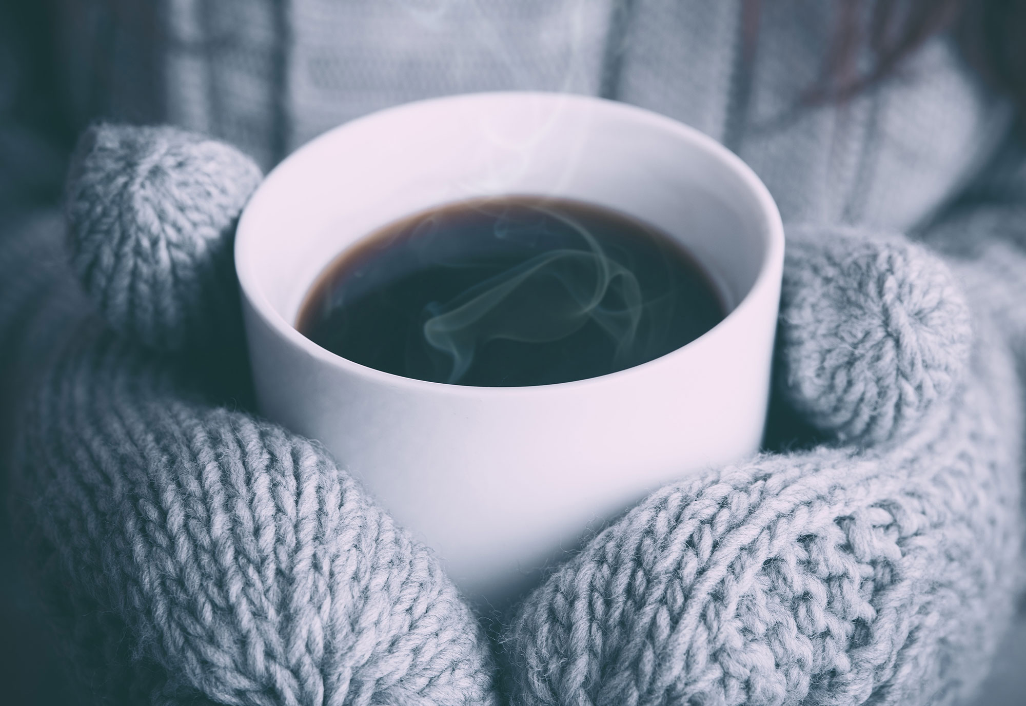 Wooly gloves holding a hot coffee