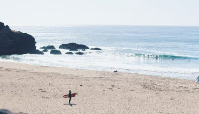 A surfer on a summer day at a beach